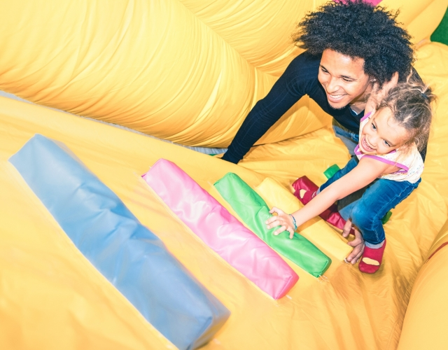 Father and daughter climbing bouncy castle