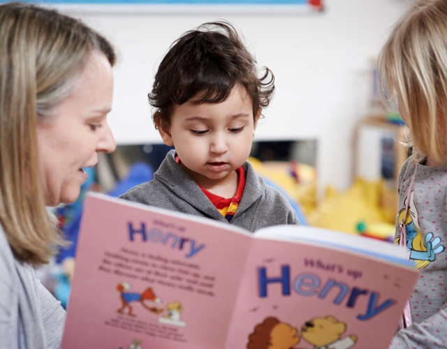 Woman reading a HENRY story book to two young children
