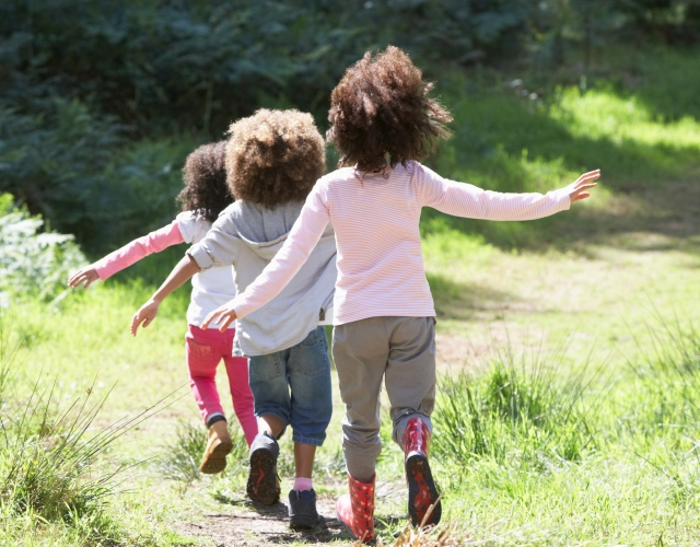 Three children running in the sunshine (feature)