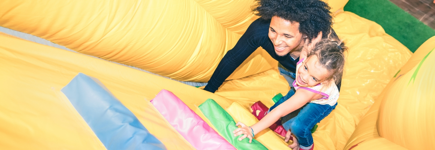 Father and daughter climbing bouncy castle together